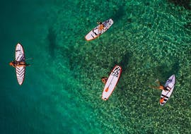 A group of friends is enjoying the clear water during their SUP Rental at Lagoa de Albufeira in Sesimbra from Meira Pro Center Sesimbra.