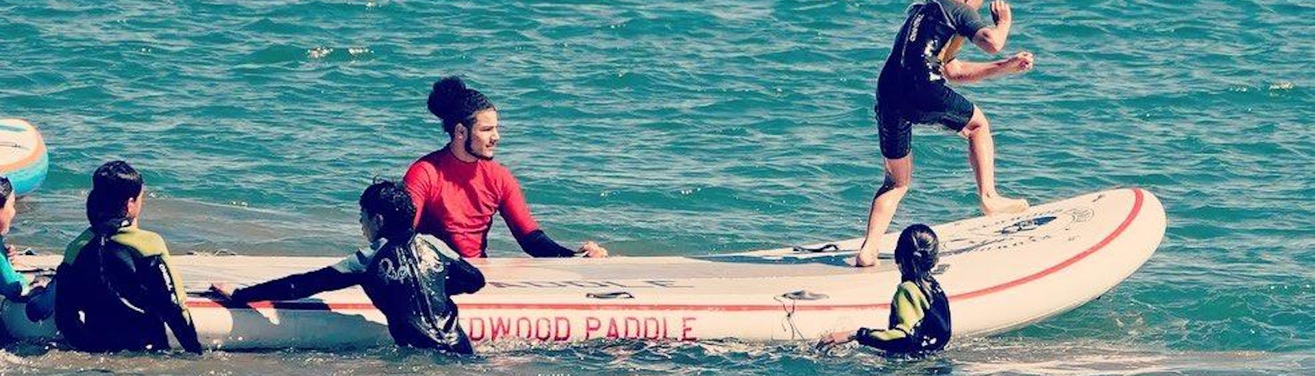 A family is enjoying a day out on the water with their Stand Up Paddleboarding Rental in Jàvea with Anywhere Watersports.