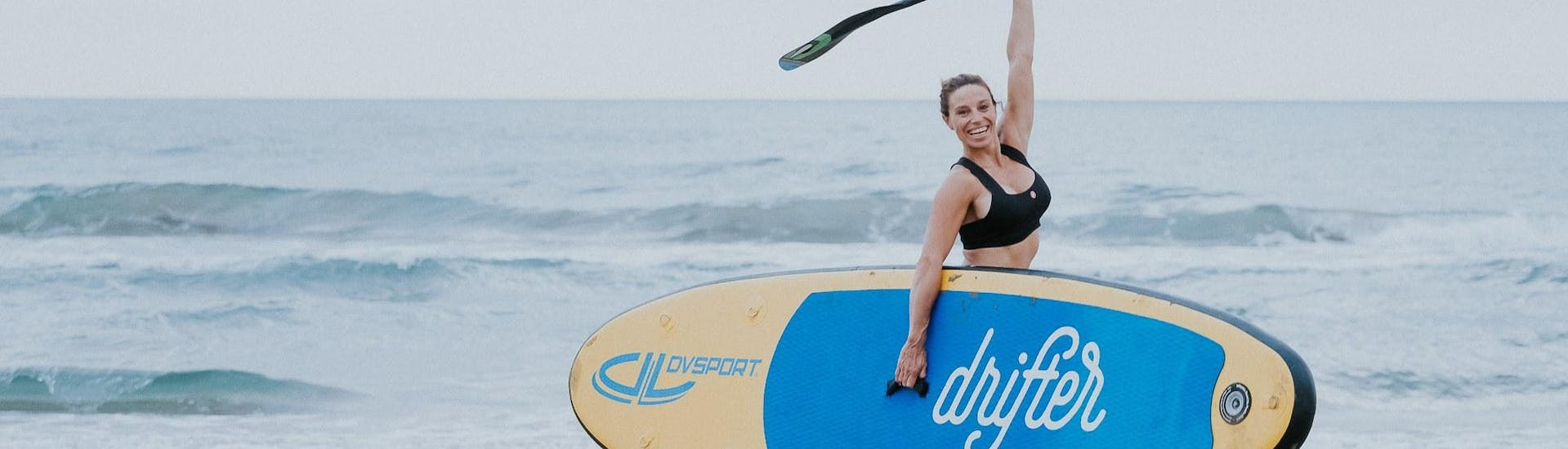 A woman is happy about her successful day in the water during her private stand up paddleboarding lesson in Jàvea with Anywhere Watersports.