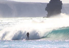 A surfer is riding a big wave under the supervision of a certified surf guide from Arrifana Surf School.