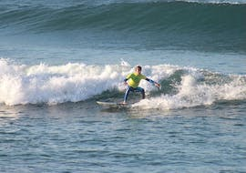 A boy has already learned a few thing in his surf lessons for all levels and is riding his first waves thanks to Linha de Onda Surf School.