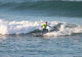 Ein Junge hat dank der Hilfe von Linha de Onda Surfing School schon Einiges im Surfkurs für alle Levels gelernt und reitet seine ersten Wellen.