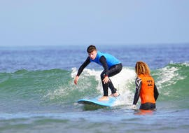 A surf instructor is giving tips to his student during the Private Surf Lessons at Gamboa Beach in Peniche with Go4Surf Peniche.