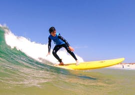 A young surfer is catching a good wave during the Intermediate Surf Lessons at Gamboa Beach in Peniche with Go4Surf Peniche.