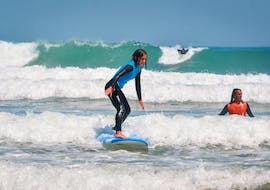 A girl is surfing her first waves during the Beginner Surf Lessons at Gamboa Beach in Peniche with Go4Surf Peniche.