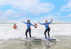 Two participants of the Surf Lessons in Gold Coast for Adults organized by the surf school Get Wet Surf School are having fun while riding a wave on the surfboard.