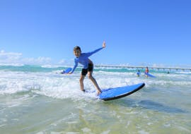 A young surfer is riding a small wave during the surf lessons in gold coast for kids organized by the surf school Get Wet Surf School.