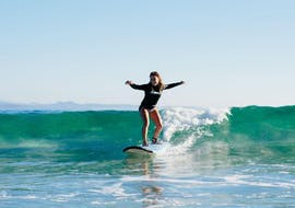 A young woman is riding a wave during her surf lessons near Byron Bay with Mojosurf.