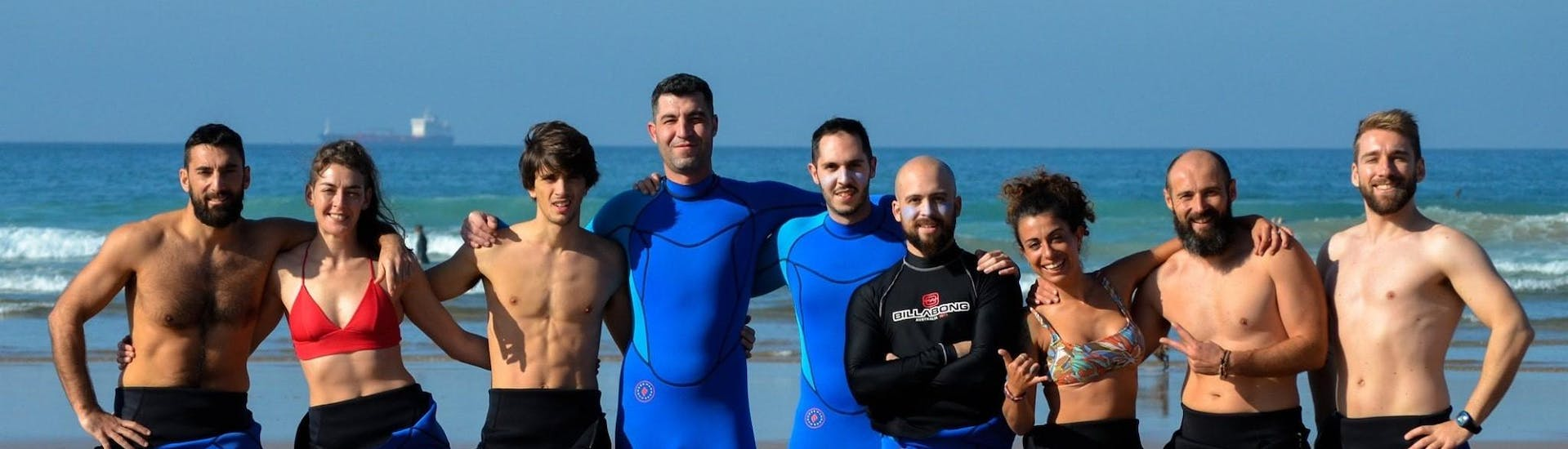A group of surfers smiles together with the surf instructors of Latas Surf into the camera during their Surfing Lessons incl. video analysis - All Levels & Ages.