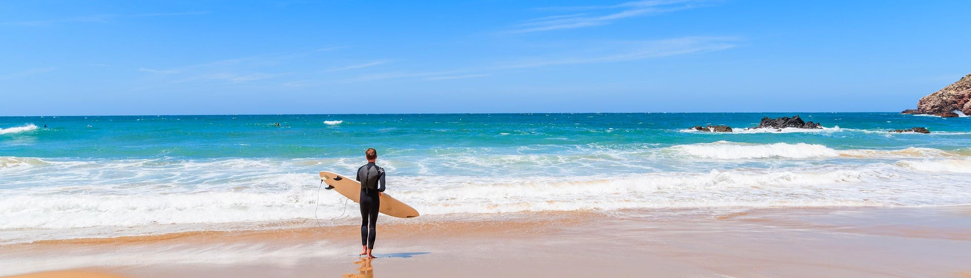A young woman surfing in the clear blue waters of the surfing and SUP hotspot of Albufeira.