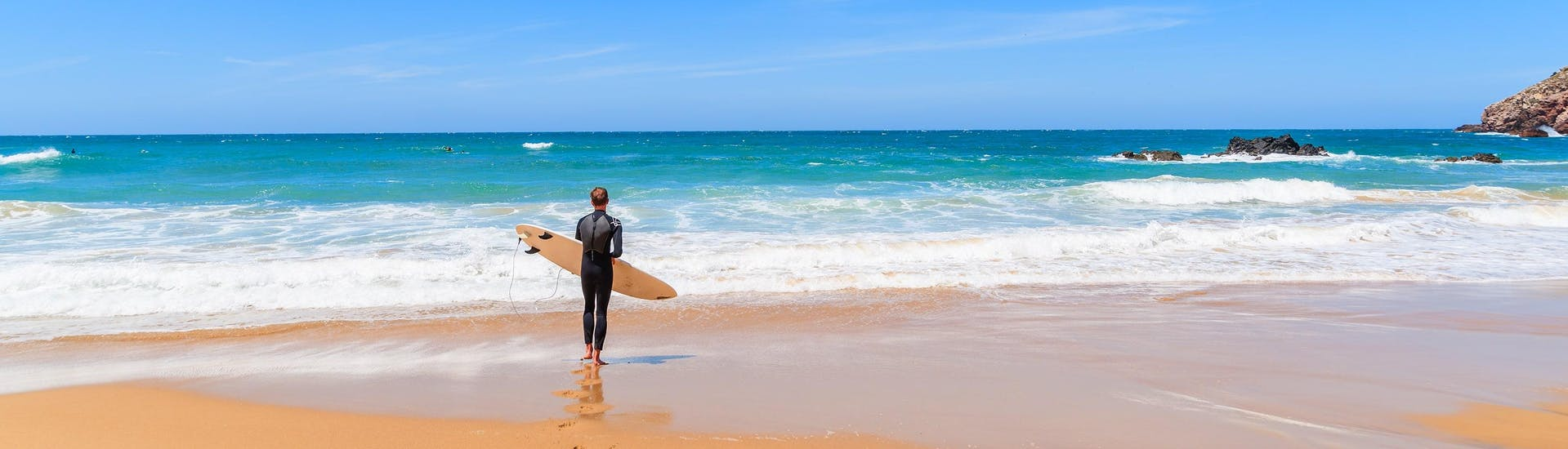 A young man dressed in a wetsuit is standing on a beach with his surfboard, looking out over the ocean as he gets ready to go surfing in Arrifana.