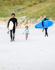 A happy family is walking along the beach as they enjoy a day of surfing in Galicia.