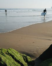 Two young men walking on the beach with water and waves are going surfing in Hendaye.