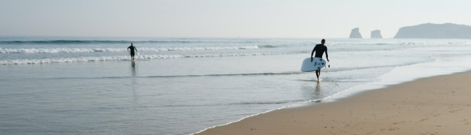 A surfer is walking on the beach of Hendaye in the early morning, one of the best places to take surfing lessons in the Basque Country.