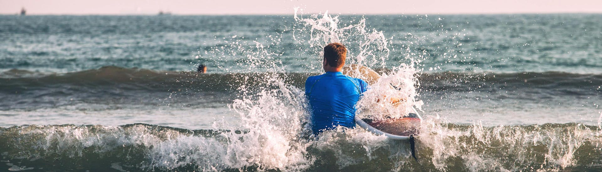 A young man is wading through the water with his board while surfing in Hossegor.