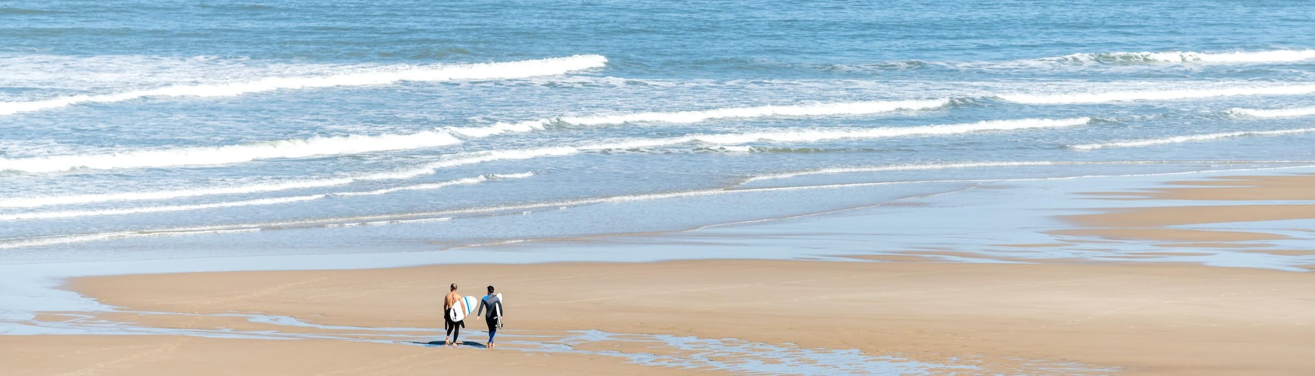 Two men are walking on the Plage Centrale of Lacanau with their surfboard under their arm, where many surfing lessons take place.