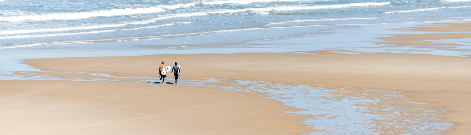 Two men are walking on the beach of Lacanau with their surfboard under their arm, where many surfing lessons take place.