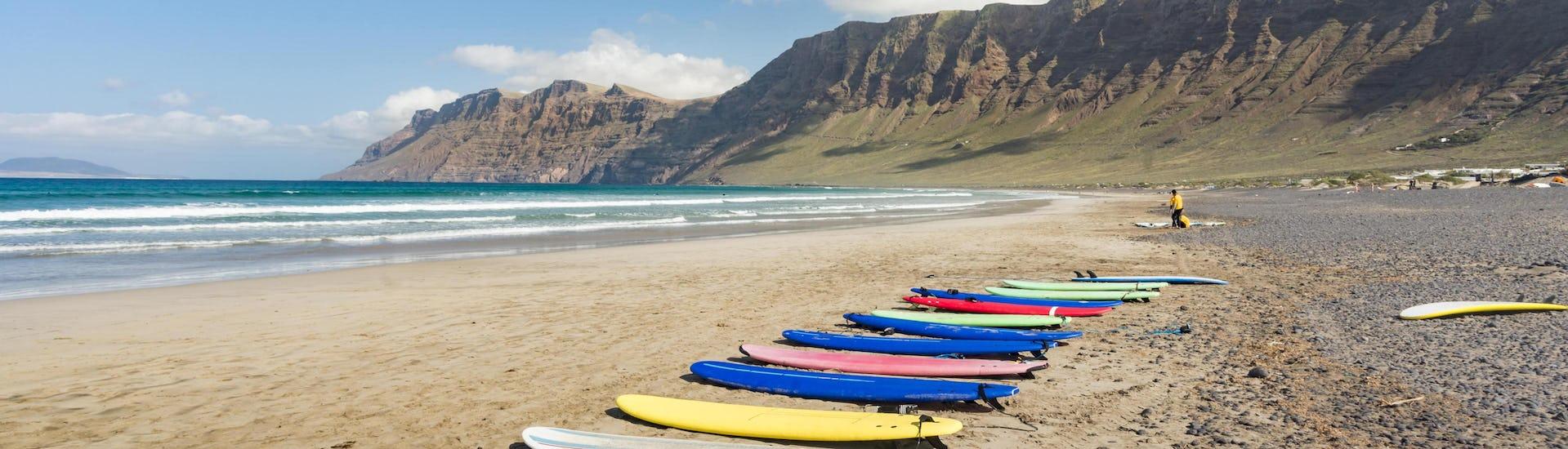 Eine Reihe Surfbretter liegt zum Surfen auf Lanzarote am Strand bereit.