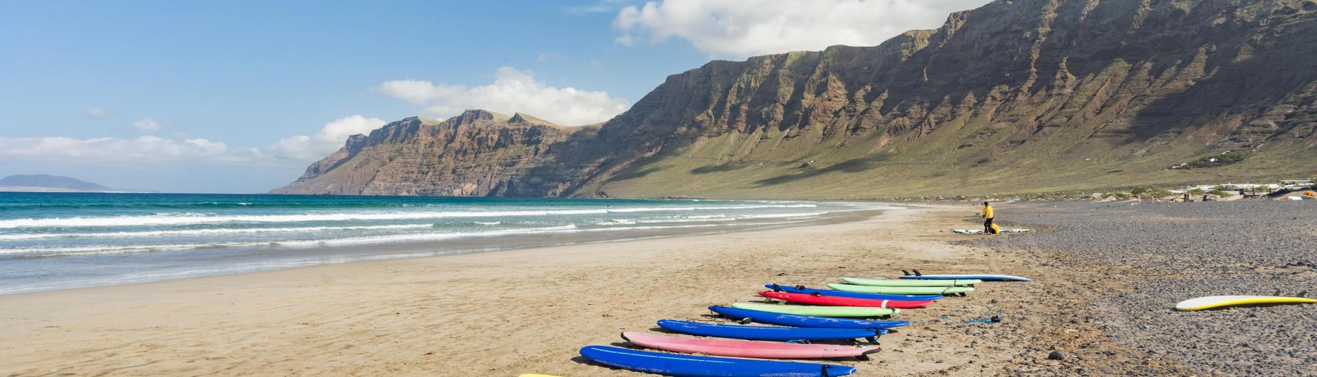 A set of surf boards is lined up on the beach Playa de Famara for people to go surfing in Lanzarote.