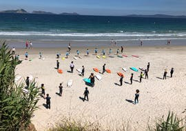 The participants of the Surfing Lessons at Playa de A Lanzada for All Levels & Ages organized by Prado Surf do a warm up on the beach.