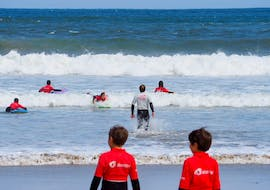 A surf instructor from Prado Surf gets into the water to help his course participants during their Surfing Lessons at Playa de Sabón for all Levels.