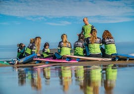 A group of surfers sit on their surfboards and listen to the surf instructor of Latas Surf during their surf course at Playa de Somo - All Levels.