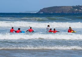 A group of surfers practice on the gentle waves of the sea during their Surfing Lessons at Playa Grande de Bastiagueiro with Prado Surf.