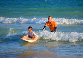 A child learns to ride its first wave with a surf instructor from Vilamoura Surf Project during the Surfing Lessons at Praia da Falésia for all Levels.