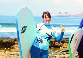A woman is posing in front of the camera and prepared to begin her beginner surf lessons with Ocean Life Surf School.