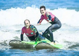 2 men are learning surf thanks to a surfing lesson  for Kids & Adults with ocean beach in Hendaye.