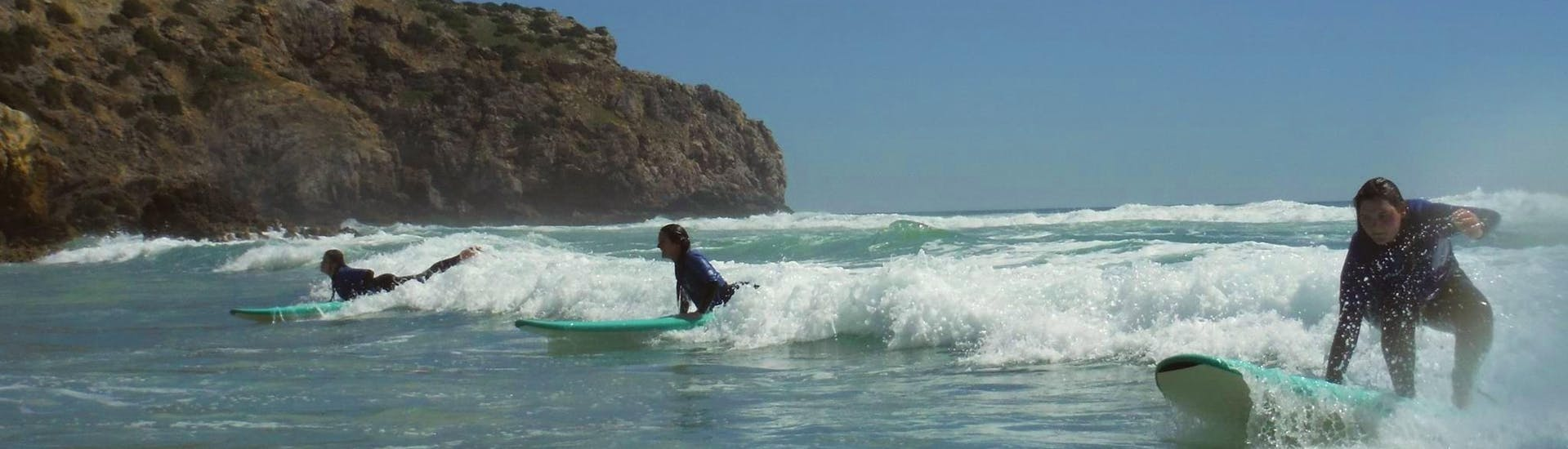 Three girls are catching the waves of the Atlantic during the Surfing Lessons for Beginners & Intermediate in the Algarve (age 12+) organized by Extreme Algarve Surf.