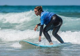 A participant of the Surfing Lessons for Beginners & Intermediate in Algarve (age 12+) with Extreme Algarve Surf is standing up on her surf board.