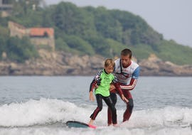 A boy is having Surfing Lessons for Kids (5-7 years) - Hendaye Beach with Gold Coast Hendaye.