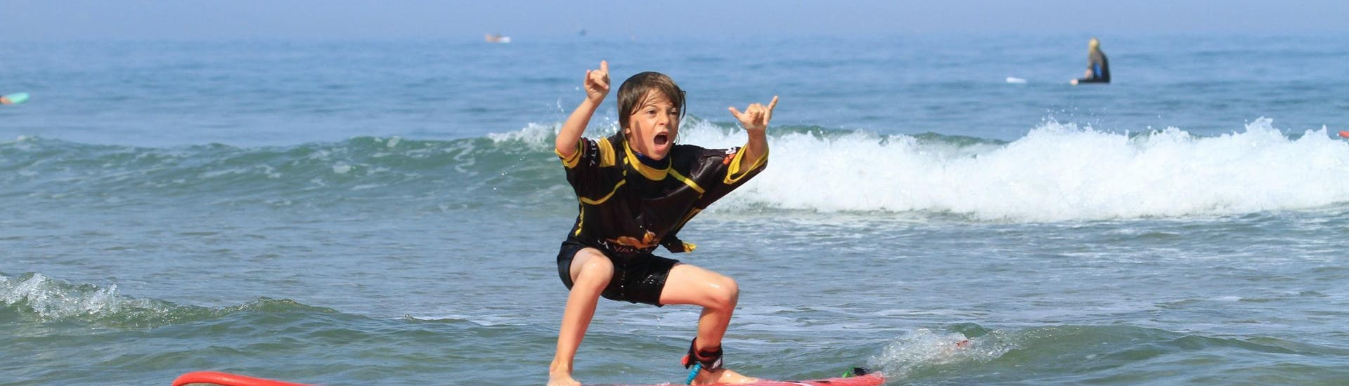 A kid is proud to be standing on their surfboard thanks to their Surfing Lessons for Kids on the Côte des Basques Beach with La Vague Basque.