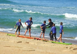 A group of kids is learning the basics of surfing on the beach with a surfing intructor from Hossegor Surf Center during their Surfing Lessons for Kids (6-11 years) - Culs Nus Beach.