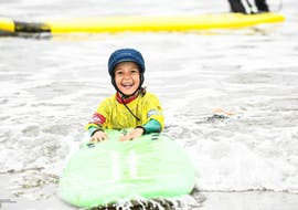 A kid is smiling as they are in the water, holding tight their surfboard, during their Surfing Lessons for Kids (6-8 years) on the Hendaye Beach with École de Surf Hendaia.