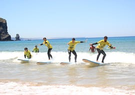 During the Surfing Lessons for Kids & Adults at Praia da Arrifana, a group of surfers is riding their first wave under the supervision of a certified surf instructor from Arrifana Surf School.