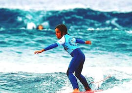 A child is starting her beginners surf lessons and moving through the water while trying to keep her balance on the board with Ocean Life Surf School.