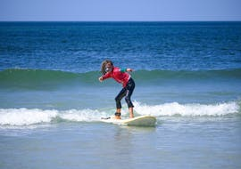 A child is standing up on the board during the surfing lessons for kids in la pointe de la torche for all levels with ESB la torche.