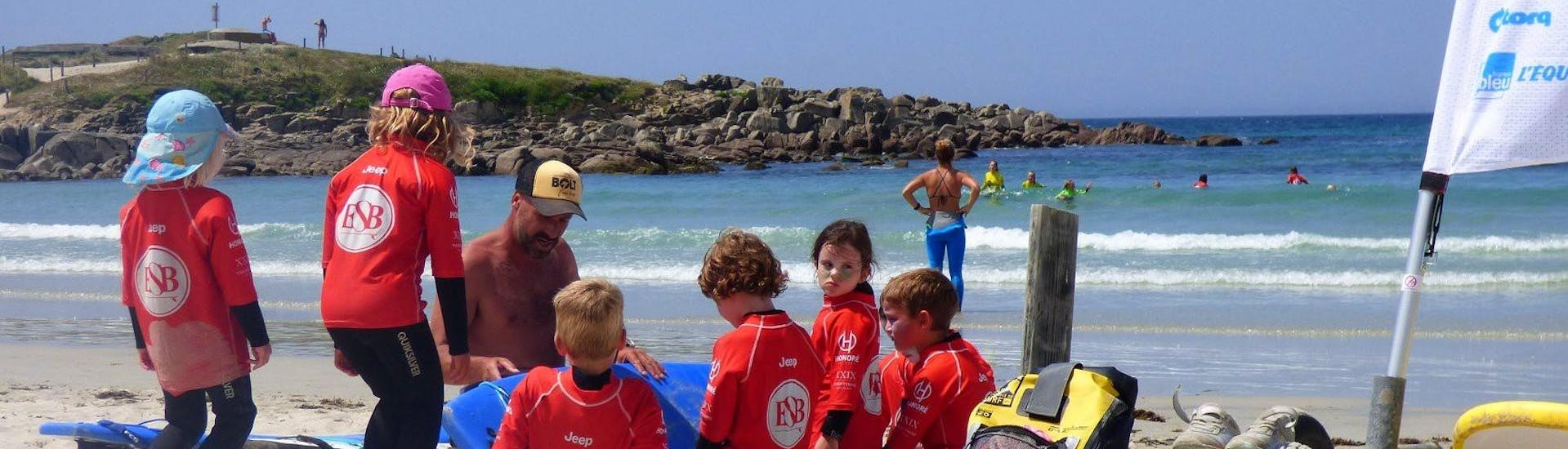 The instructor is giving safety instructions on the beach during the surfing lessons for kids in la pointe de la torche with ESB la torche.