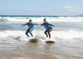 Two participants surfing the waves during a group lesson in Famara beach with Surf&SUP School3s Lanzarote.