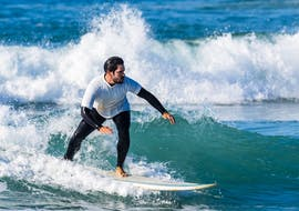 A young man from the Gecko Surf School surfs on the Costa da Caparica.