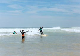 A surfer is learning how to surf a wave under the supervision of their surf instructor from the surf school ESCF Hossegor during their Surfing Lessons on the Gravière Beach.