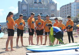 Surfers are on the beach listening to the instructions of their surf instructor during their surfing lessons on Hendaye Beach during low season with the surf school École de surf Hendaia.