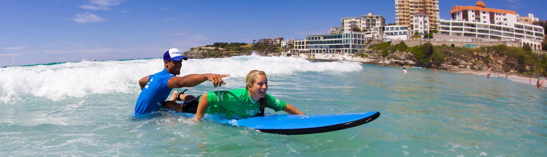During the Surfing Lessons in Bondi Beach for Teens & Adults - Beginner, a young woman is having great time whilst learning how to surf under the guidance of an experienced surf instructor from Let's Go Surfing.
