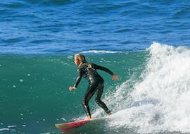 A young girl is riding across the waves of the Atlantic during her surfing lessons in Madeira for beginners and intermediates with Madeira New Wave.