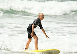 A girl is having Surfing Lessons on the Marbella Beach with the Eco surf school in Biarritz.