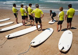 """Surfers are on the beach listening to their surf intructor from the surf school Le Club de la Glisse prior to the start of their Group Surfing Lessons """"À la carte"""" on the Marinella Beach in Anglet."""