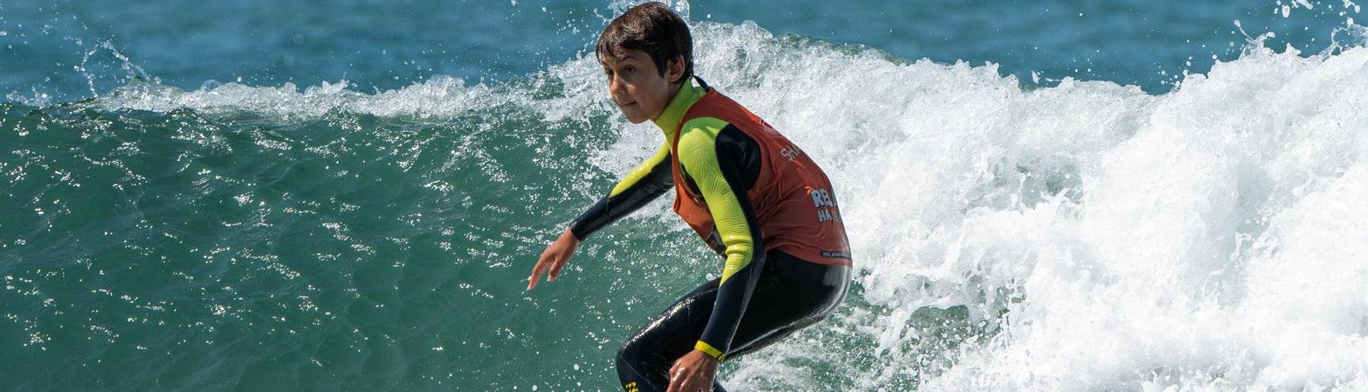 Under the guidance of an experienced surf instructor from Surfaventura, a boy is fully focused on riding his first wave during the surfing lessons on Matosinhos Beach.