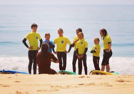 A group is listening the instructor on the beach during the Surfing Lessons on Salie Beach for All Levels with Pyla surf school.